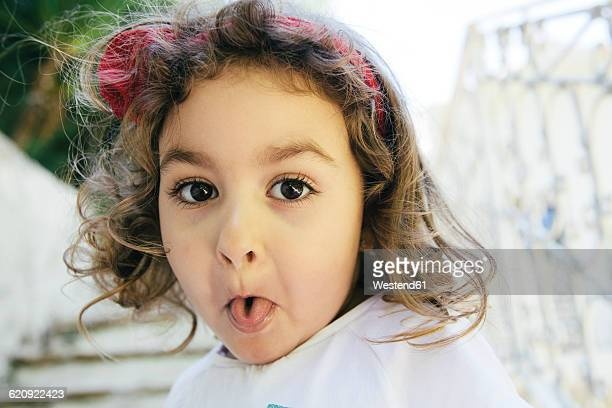 Portrait of little girl sticking out tongue