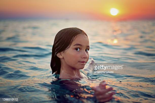 portrait of little girl swimming in the ocean - bottomless girl stock pictures, royalty-free photos & images