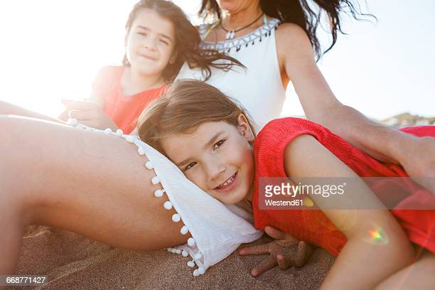 Portrait of little girl together with mother and sister on the beach