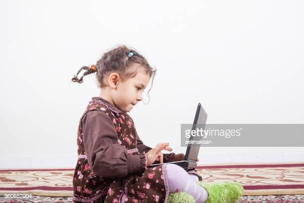 Portrait Of Little Girl Using Notebook Computer