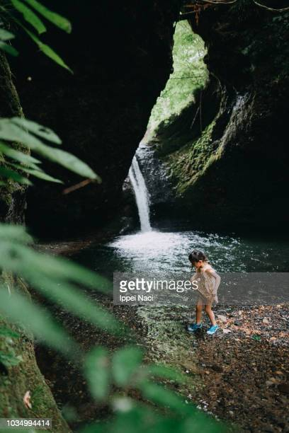 Portrait of little girl walking in river water running from waterfall, Japan