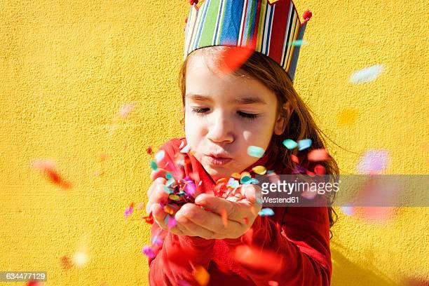 portrait of little girl wearing paper crown blowing confetti - flying solo after party bildbanksfoton och bilder