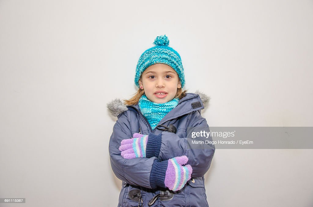 74ffea639e5e Portrait Of Little Girl Wearing Warm Clothes Against White Background -  stock photo