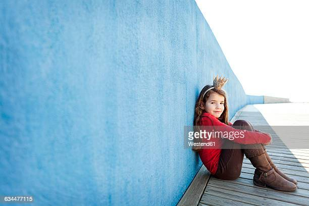 portrait of little girl with a crown leaning against blue wall - princess stock pictures, royalty-free photos & images