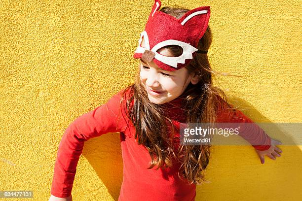 Portrait of little girl with animal mask in front of yellow wall