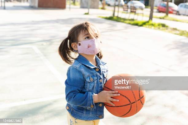 portrait of little girl with basketball wearing protective mask - face guard sport stock pictures, royalty-free photos & images