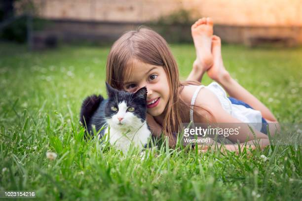 portrait of little girl with cat lying on a meadow - lying on front stock pictures, royalty-free photos & images