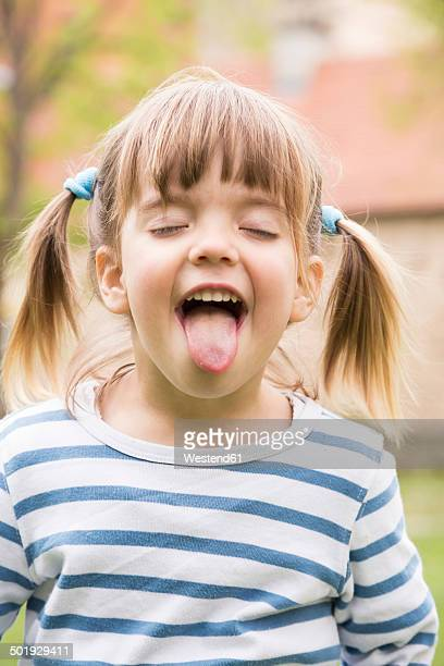 portrait of little girl with closed eyes and outstretched tongue - little girl sticking out tongue stock photos and pictures
