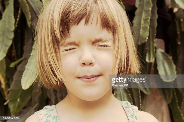 Portrait of little girl with closed eyes pouting mouth