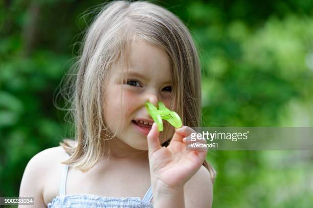 Portrait of little girl with clothes peg on her nose