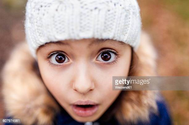 portrait of little girl with eyes wide open - braune augen stock-fotos und bilder