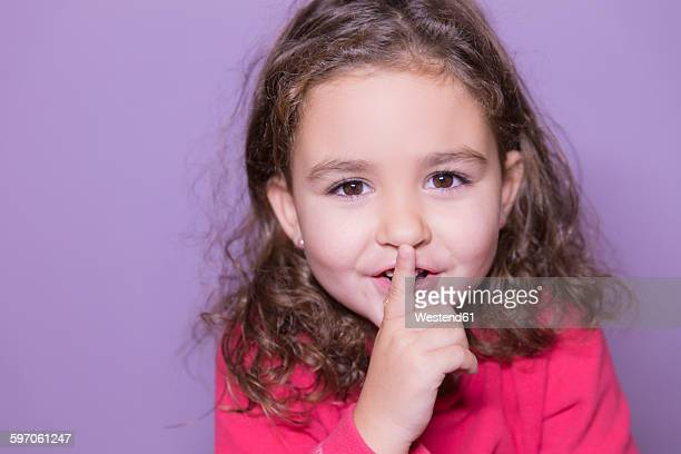 Portrait of little girl with finger on her mouth