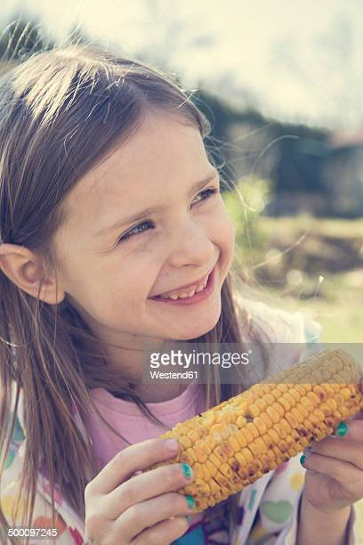 Portrait of little girl with grilled corn cob