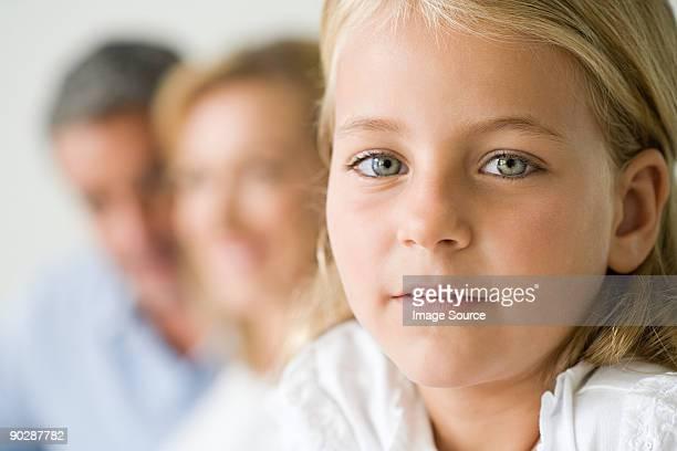 Porträt von kleinen Mädchen mit ihren Eltern im Hintergrund