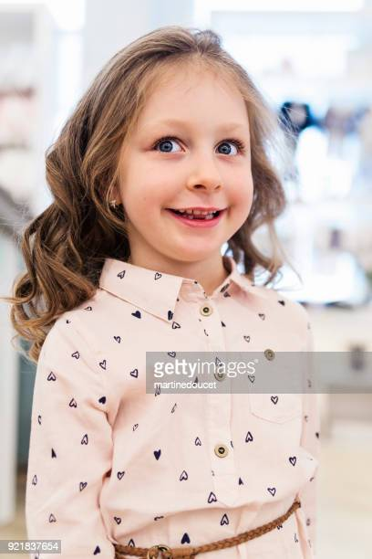 Portrait of little girl with missing tooth in a store.