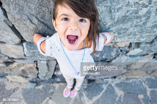 girls with mouths open portrait of little girl with mouth open in front of a rock 3844