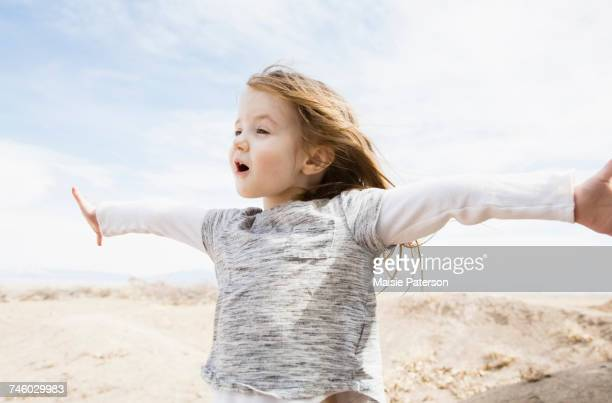 Portrait of little girl (4-5) with outstretched arms and open mouth in field