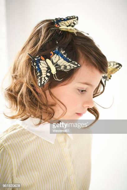 Portrait of little girl with toy butterflies in her hair