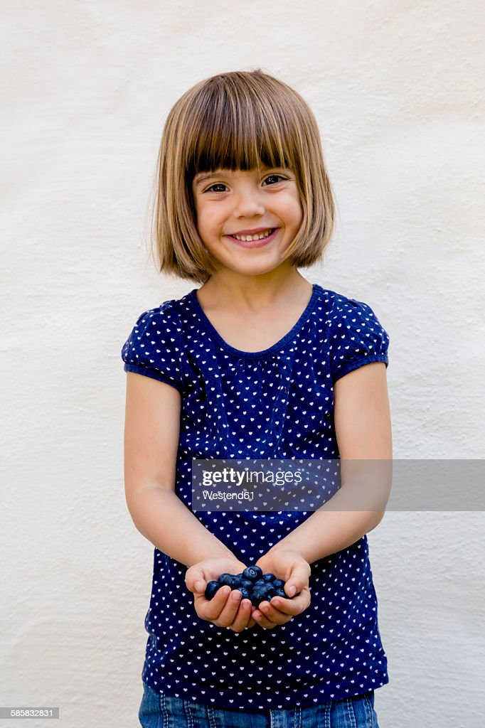Portrait of little girl with two handfuls of blueberries : Stock-Foto