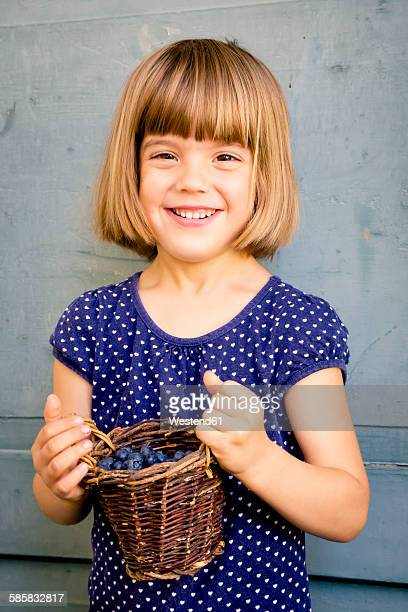Portrait of little girl with wickerbasket of blueberries
