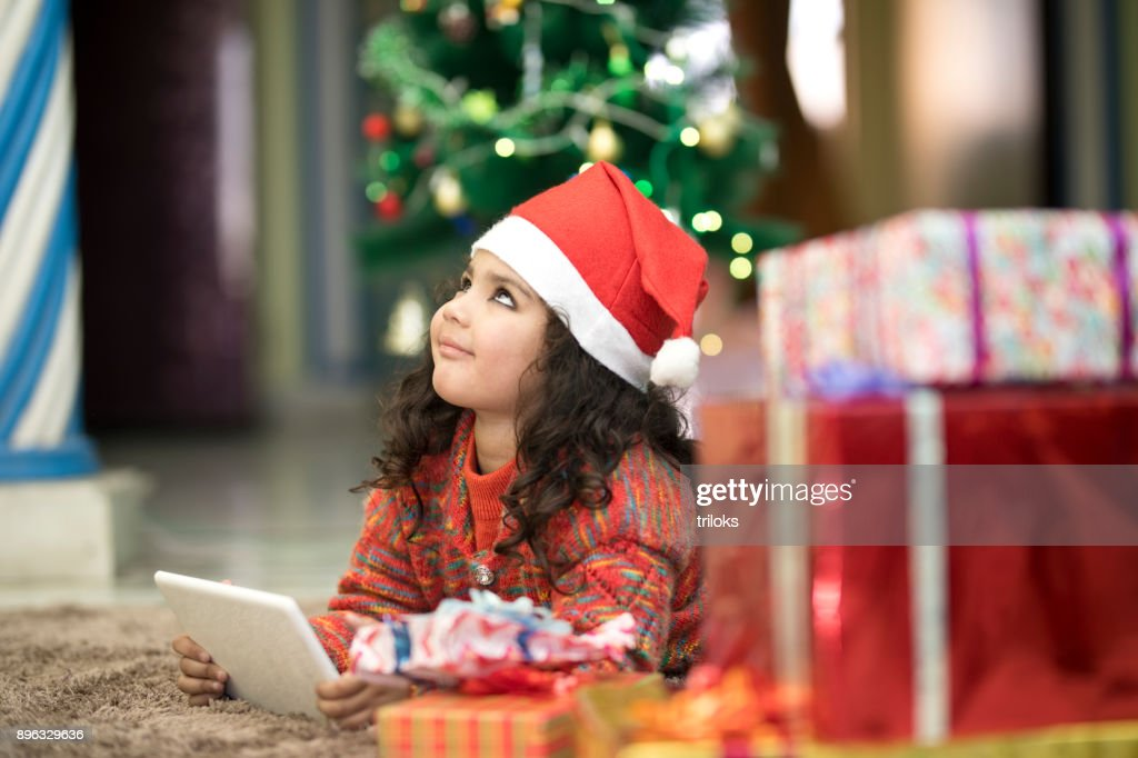 3b6560f9cb0 ... portrait of little indian girl in santa hat using digital tablet stock  photo