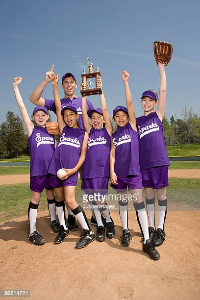 Portrait of little league softball team with coach holding trophy