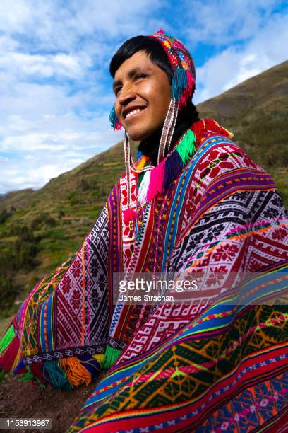 portrait of local man in colourful traditional local dress including festooned woolen hat and poncho, against green valley background and blue sky, chumbe community, lamay, sacred valley, peru (model release) - cultura peruana fotografías e imágenes de stock
