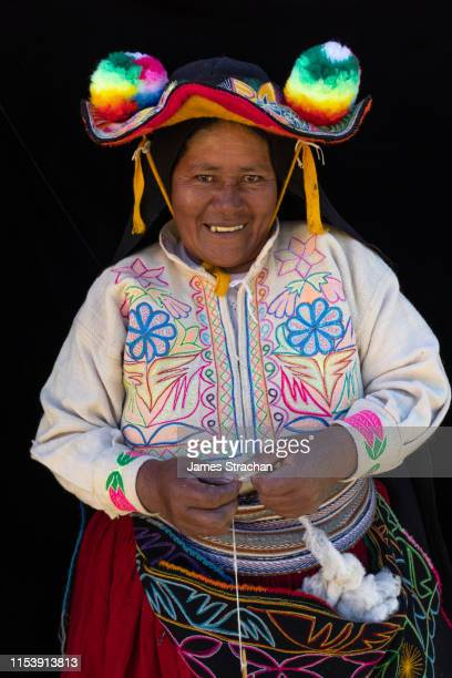 portrait of local woman in colourful local traditional dress smiling as she spins wool by their house, llachon island, lake titicaca - james strachan stock pictures, royalty-free photos & images