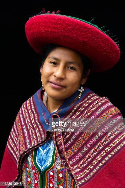 portrait of local woman in colourful, predominantly red, traditional local dress and hat, chinchero, sacred valley, peru (model release) - james strachan stock pictures, royalty-free photos & images