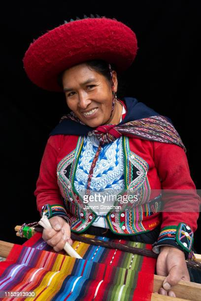 portrait of local woman weaver at her loom in colourful, predominantly red, traditional local dress and hat, chinchero, sacred valley, peru (model release) - james strachan stock pictures, royalty-free photos & images