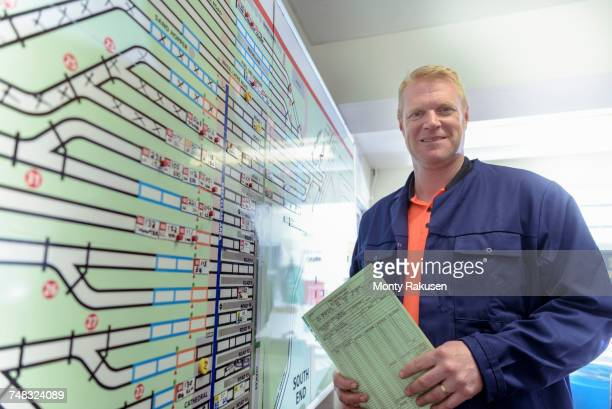 Portrait of locomotive engineer with engine shed plans in train works