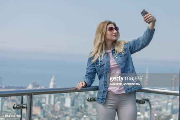 Portrait of long woman taking selfie above city view