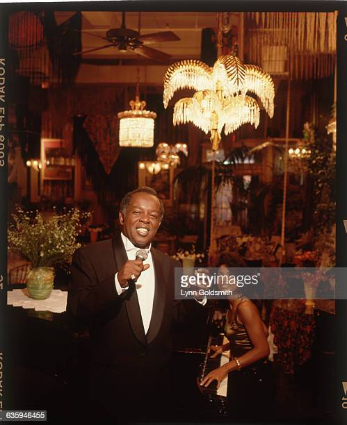 Portrait of Lou Rawls performing in a cocktail lounge A woman is visible playing piano in the background Photograph 1989