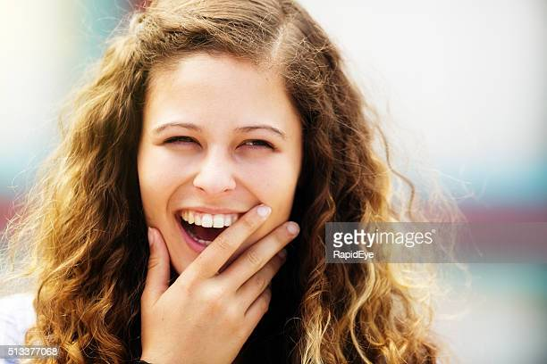 Portrait of lovely, laughing, curly-haired girl in sunshine