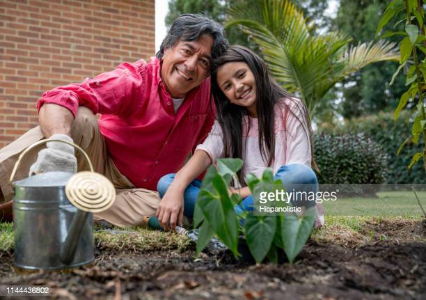 Portrait of loving grandfather and granddaughter smiling at camera while gardening
