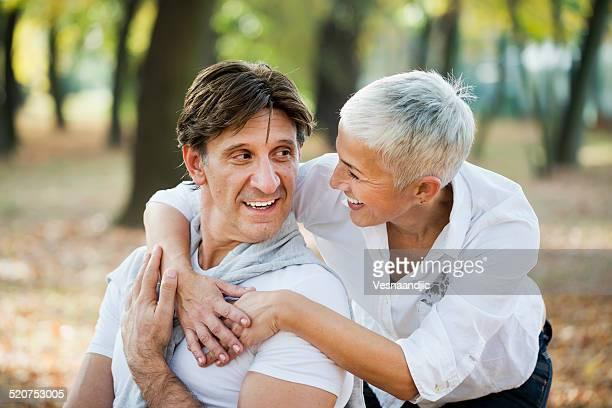Portrait d'amoureux femme d'âge mûr embrassant homme par derrière