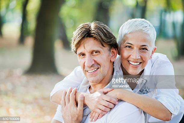 Portrait of loving mature woman embracing man from behind