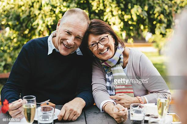 Portrait of loving senior couple having desserts at cafe table