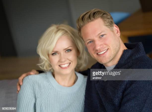 Portrait d'aimer le jeune couple assis sur le canapé à la maison en regardant sourire caméra