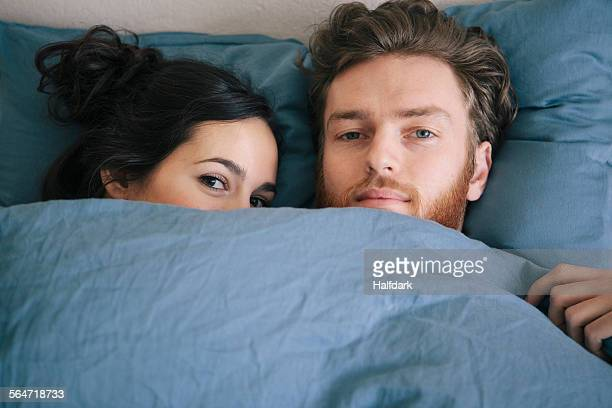 portrait of loving young couple under duvet in bed - couple lit photos et images de collection