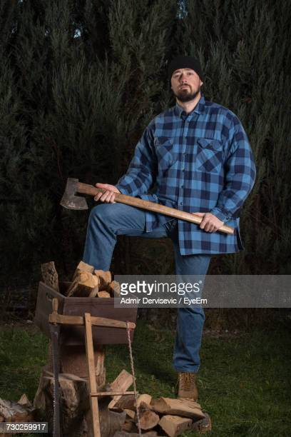 Portrait Of Lumberjack Holding Axe Against Trees At Forest