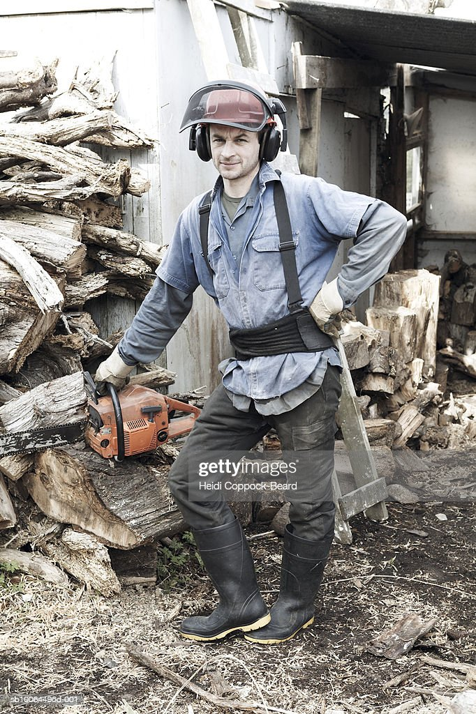 Portrait of lumberjack near woodpile outdoors : Stock Photo
