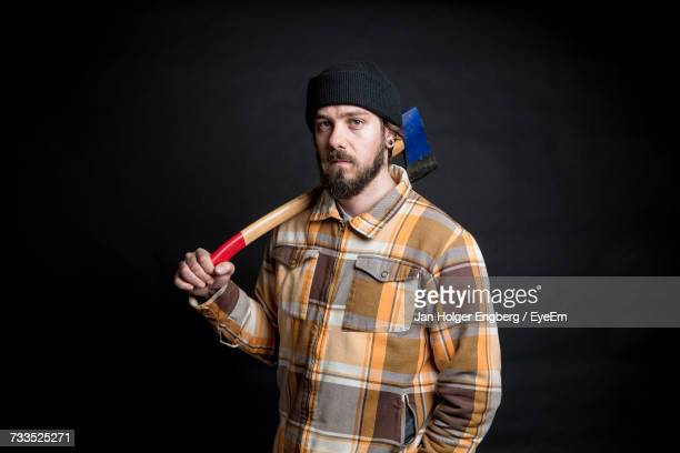 Portrait Of Lumberjack With Axe Over His Shoulder Against Black Background