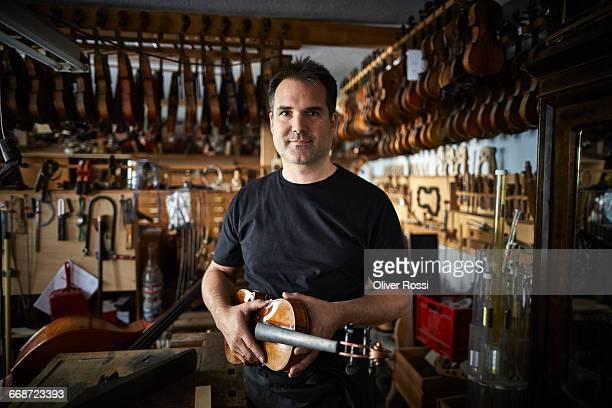 Portrait of luthier in workshop holding violin
