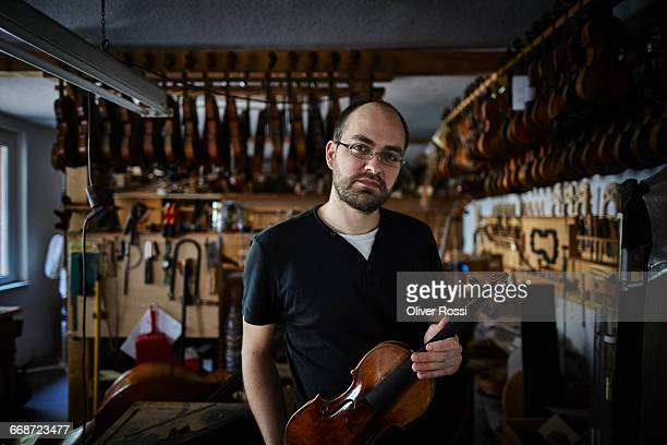 portrait of luthier in workshop holding violin - instrument maker stock photos and pictures