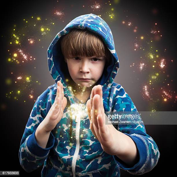Portrait Of Magician Boy With Sparkles Against Gray Background