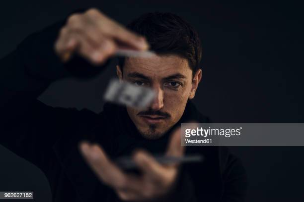 portrait of magician conjuring with playing cards - illusion stock pictures, royalty-free photos & images