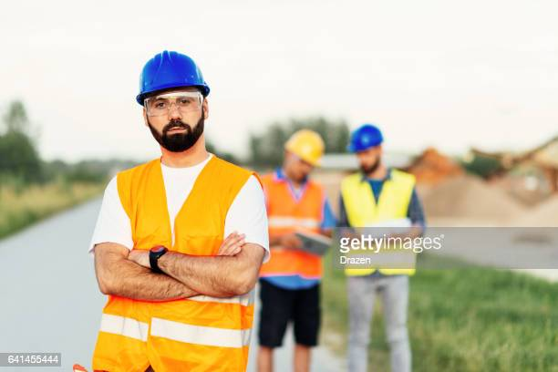Portrait of main engineer with beard and sunglasses on construction site
