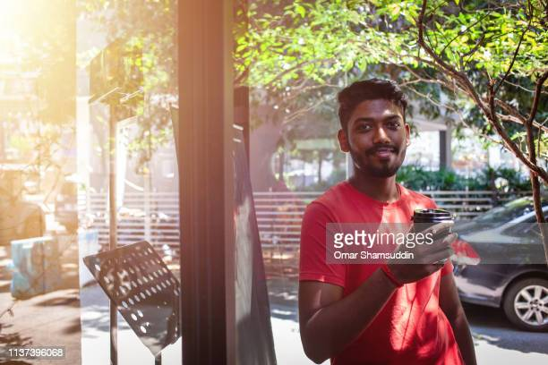 portrait of malaysian indian man with a coffee cup outside a cafe - omar shamsuddin stock pictures, royalty-free photos & images