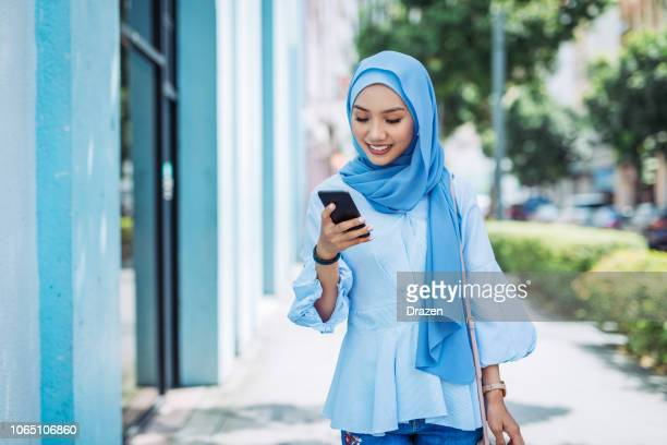 portrait of malaysian woman with blue hijab using phone - malaysian culture stock pictures, royalty-free photos & images